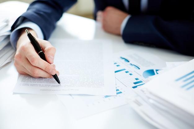Primer plano de ejecutivo subrayando un documento