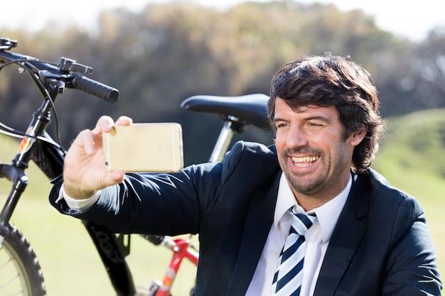 Primer plano de ejecutivo tomándose una foto con su bicicleta