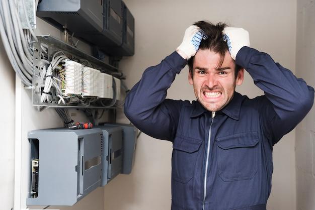 Primer plano de electricista masculino frustrado de pie cerca de tablero eléctrico