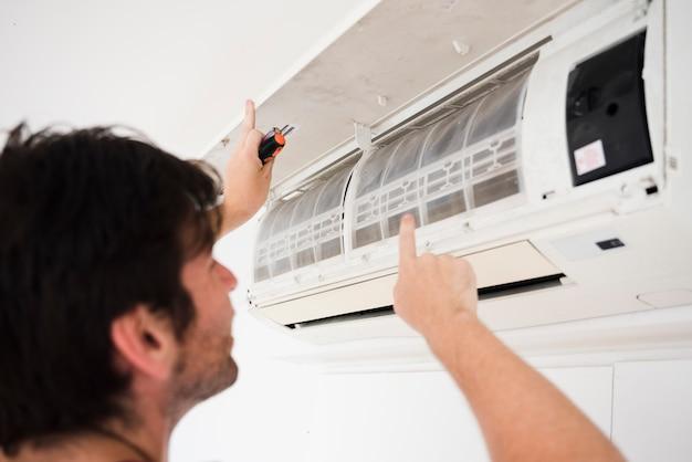 Primer plano de electricista reparando aire acondicionado