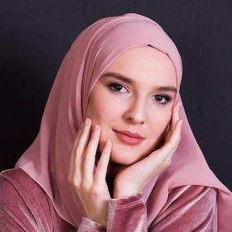 Primer plano de la elegancia joven mujer vistiendo hijab mirando a cámara