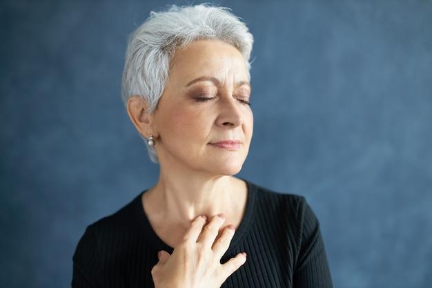 Primer plano de elegante atractiva mujer de mediana edad con canas y arrugas, cerrando los ojos y sonriendo, tocando el cuello, aplicando crema anti envejecimiento