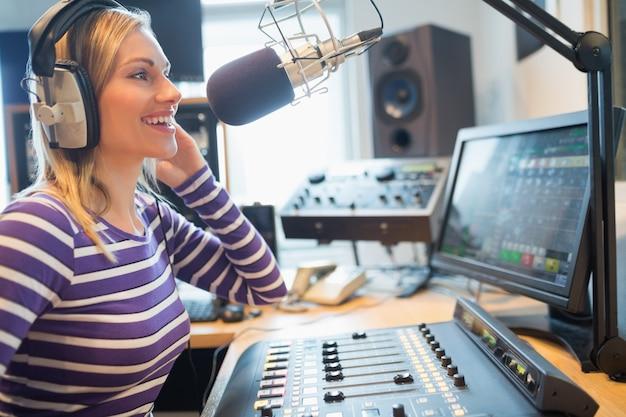 Primer plano de una emisora de radio femenina feliz transmitida a través de un micrófono en el estudio