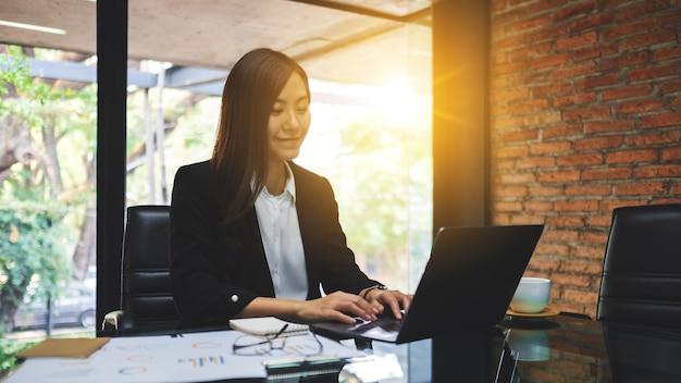 Primer plano de una empresaria asiática usando y escribiendo en la computadora portátil mientras trabajaba en la oficina