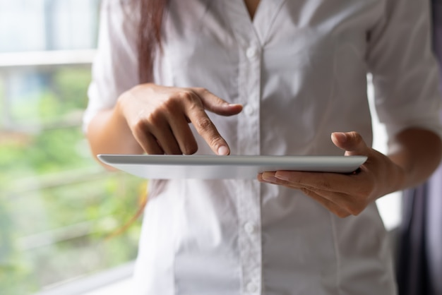 Primer plano de empresaria en camisa blanca utilizando dispositivo moderno