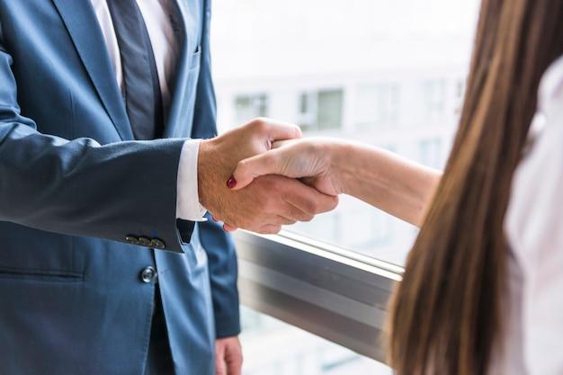 Primer plano de la empresaria y empresario agitando las manos