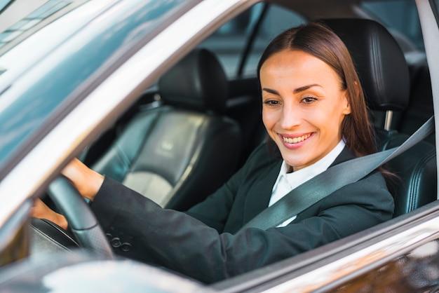 Primer plano de una empresaria joven sonriente conduciendo un coche