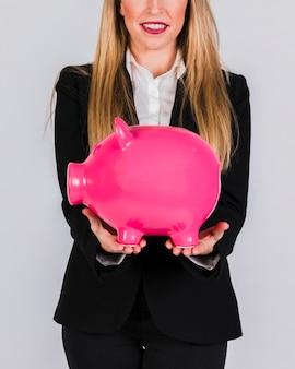 Primer plano de una empresaria joven sonriente sosteniendo piggybank de cerámica rosa en la mano