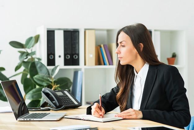 Primer plano de una empresaria mirando portátil escribiendo notas en diario con lápiz