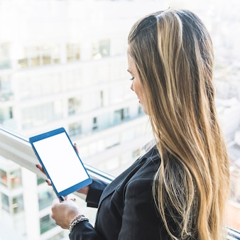Primer plano de una empresaria mirando tableta digital con pantalla de visualización en blanco