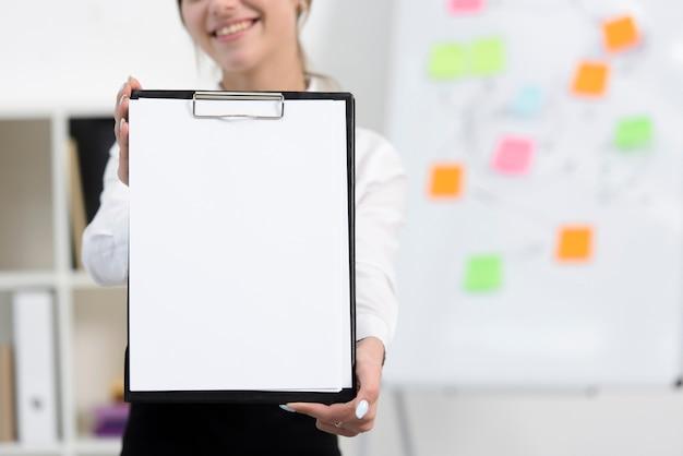 Primer plano de empresaria mostrando papel blanco en portapapeles