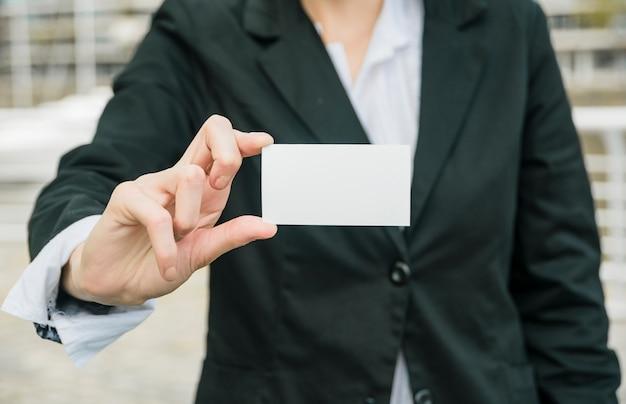Primer plano de una empresaria mostrando tarjeta de visita en blanco blanco