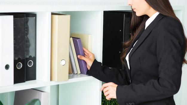 Primer plano de una empresaria quitando libro de estante