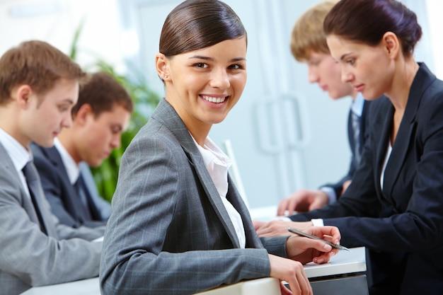 Primer plano de empresaria sonriente sujetando un bolígrafo