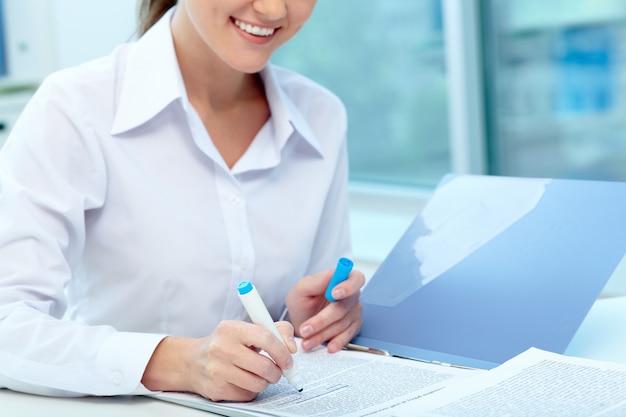 Primer plano de empresaria subrayando un informe