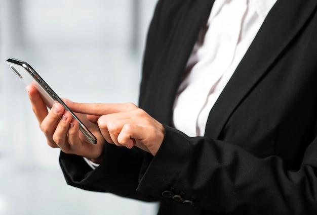 Primer plano de una empresaria tocando teléfono inteligente con el dedo