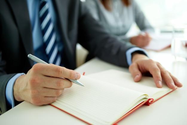 Primer plano de empresario con un bolígrafo y un cuaderno abierto
