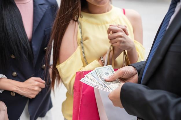 Primer plano del empresario coqueteo dando dólares en efectivo a dos mujeres jóvenes para ir de compras