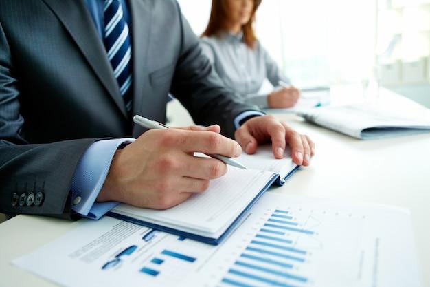Primer plano de empresario escribiendo en una reunión