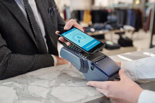 Primer plano del empresario irreconocible de pie en el mostrador en la tienda y pagando con el teléfono inteligente en línea