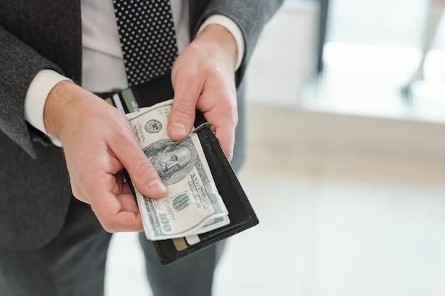 Primer plano del empresario irreconocible en traje obteniendo dinero de la billetera con tarjetas de crédito y descuento