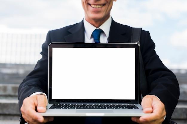 Primer plano de un empresario maduro feliz mostrando portátil con pantalla en blanco en blanco