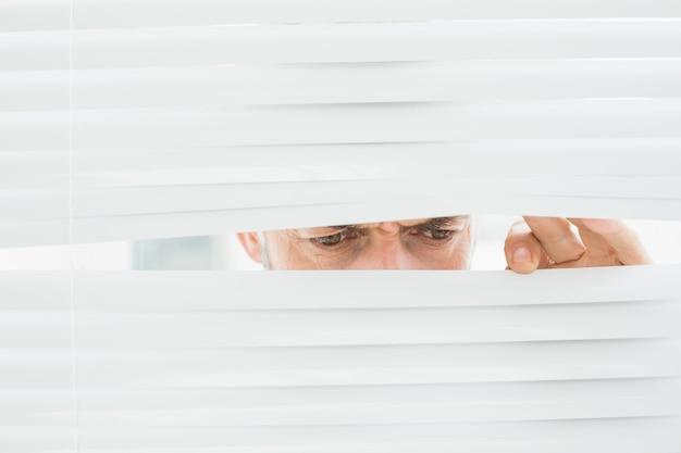 Primer plano de un empresario maduro mirando a través de las persianas