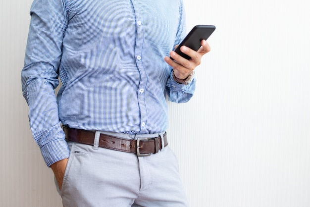 Primer plano de empresario mensajes de texto en el teléfono inteligente