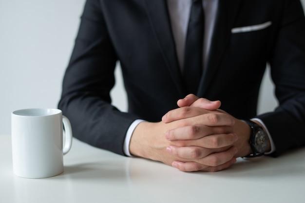 Primer plano de empresario reflexivo con las manos juntas