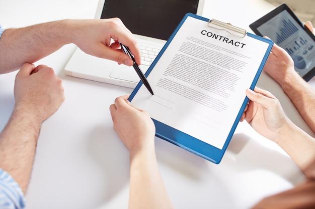 Primer plano de empresario señalando donde firmar