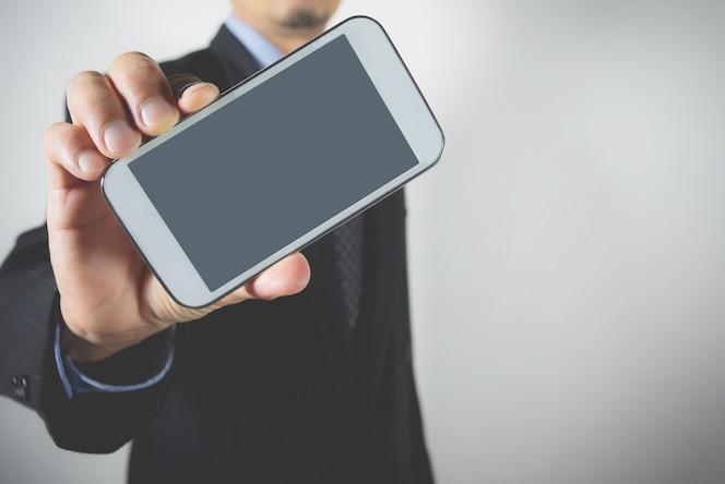 Primer plano empresario sosteniendo teléfono inteligente. hombre de negocios que sostiene la maqueta de la pantalla del dispositivo para arriba.