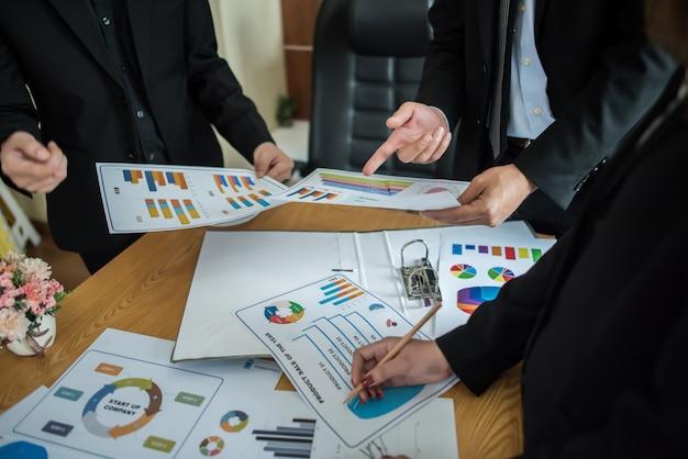 Primer plano de empresarios que trabajan con documentos comerciales durante la discusión en la reunión.