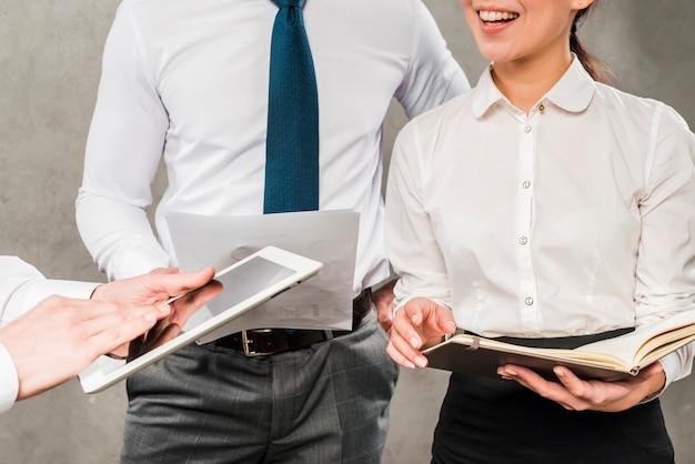 Primer plano de empresarios trabajando juntos contra la pared gris