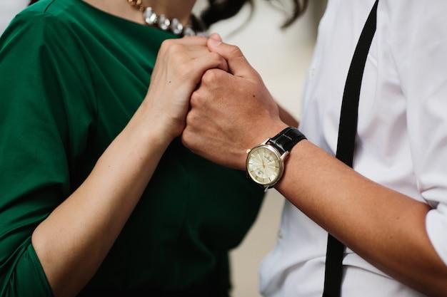 Primer plano de enamorados cogiéndose las manos