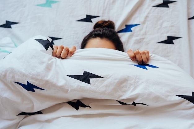 Primer plano de encantadora joven se encuentra en la cama cubierta con una manta.
