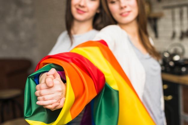 Primer plano de una encantadora pareja de jóvenes lesbianas tomándose las manos con la bandera de orgullo envuelto lgbt