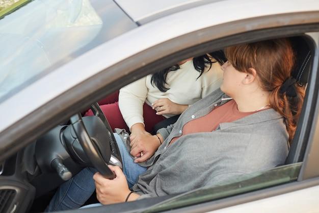 Primer plano de la encantadora pareja de lesbianas cogidos de la mano durante su viaje en coche