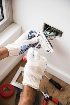 Primer plano del enchufe de fijación de la mano del electricista en la pared blanca en casa