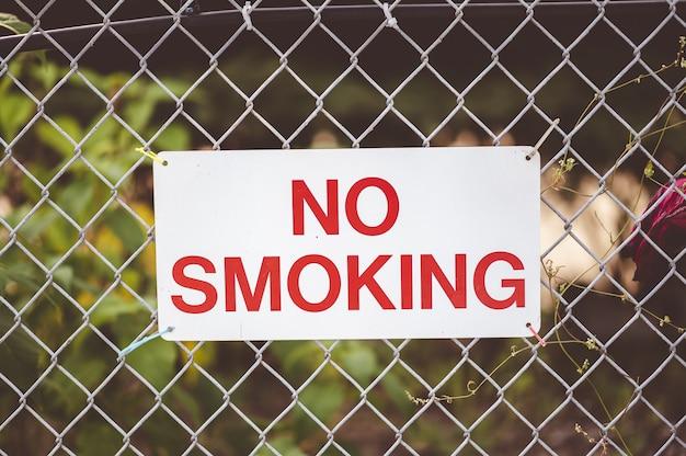 Primer plano de enfoque de letrero de 'no fumar' colgado junto a la valla