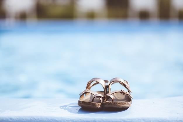 Primer plano de enfoque de sandalias de cuero tendido junto a la piscina