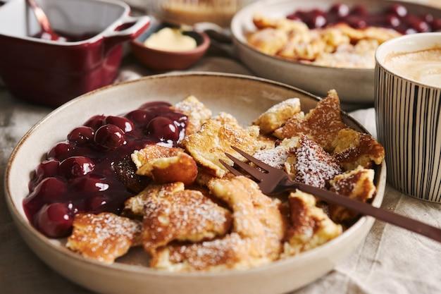 Primer plano de enfoque selectivo de deliciosos panqueques esponjosos con cereza y azúcar en polvo