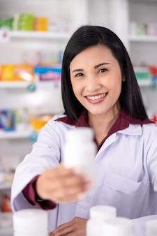 Primer plano y enfoque selectivo en el ojo farmacéutico femenino asiático mostrar medicina botella blanca en farmacia '