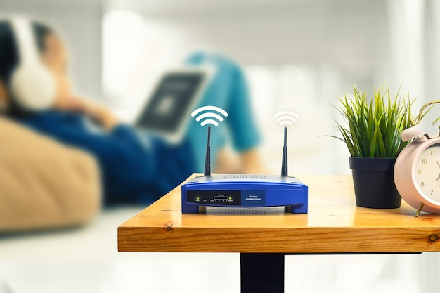 Primer plano de un enrutador inalámbrico y un hombre que usa un teléfono inteligente en la sala de estar en la oficina en casa