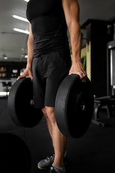Primer plano de entrenamiento de hombre en forma en el gimnasio