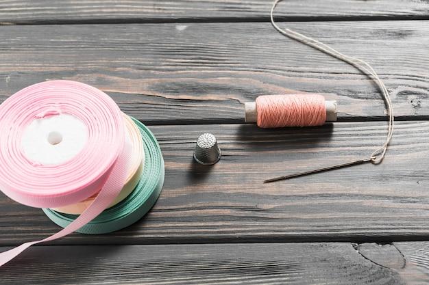 Primer plano de equipo de costura artesanal con cintas enrolladas.