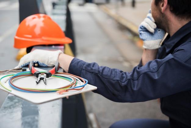 Primer plano de equipo eléctrico y electricista en calle.