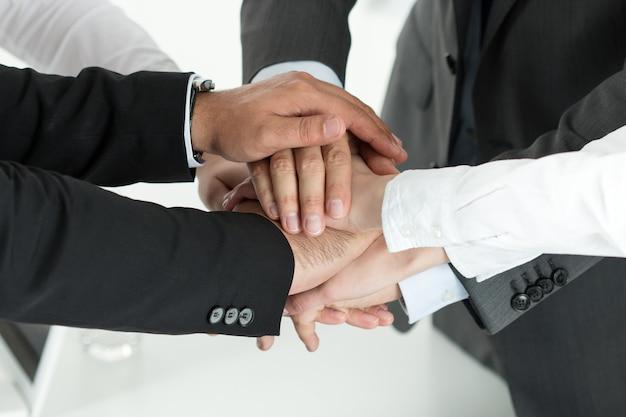 Primer plano del equipo de negocios que muestra unidad con poner sus manos juntas una encima de la otra. concepto de trabajo en equipo.