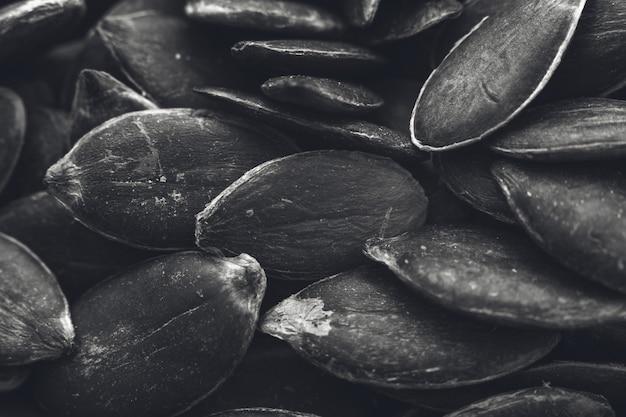Primer plano en escala de grises de un montón de semillas de calabaza, ideal para un fondo blanco y negro