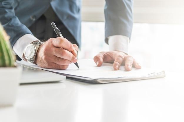Primer plano de la escritura del hombre de negocios en el documento con la pluma en el escritorio