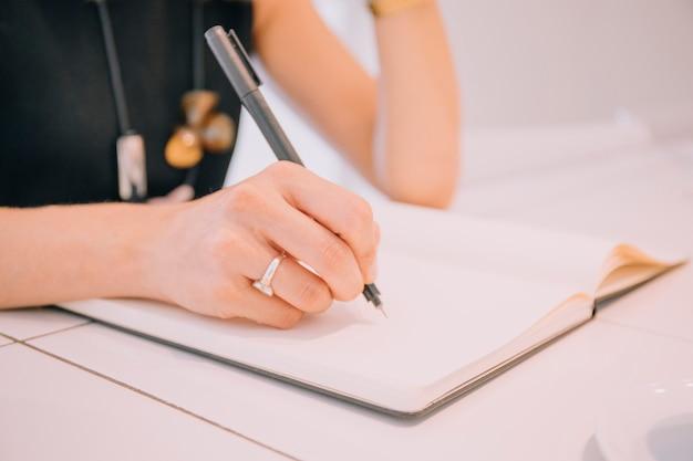 Primer plano de la escritura de la mano de la empresaria con la pluma en el diario